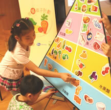 Children in Hong Kong learn about healthy eating habits by sticking food stickers on the food pyramid