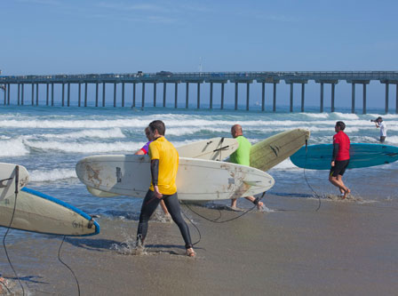 Colleagues hit the beach with their surfboards at a recent fund-raiser in La Jolla